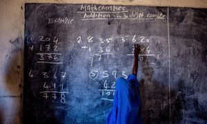 A young girl writes on a chalkboard at a primary school in Nigeria.
