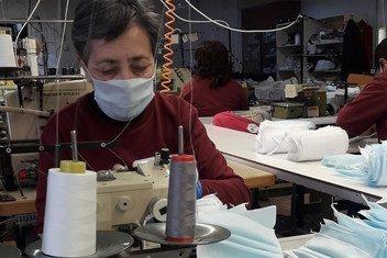 Trabajadora de una fábrica de ropa en Armenia cose máscaras para los trabajadores de salud durante la pandemia de COVID-19