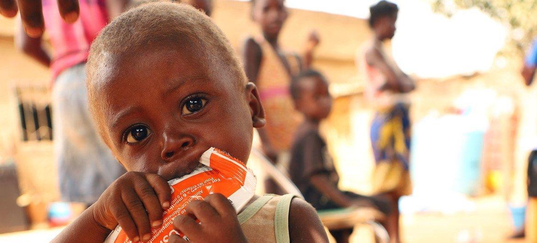 Criança de dois anos come uma pasta nutricional depois de ser testada para desnutrição em Angola