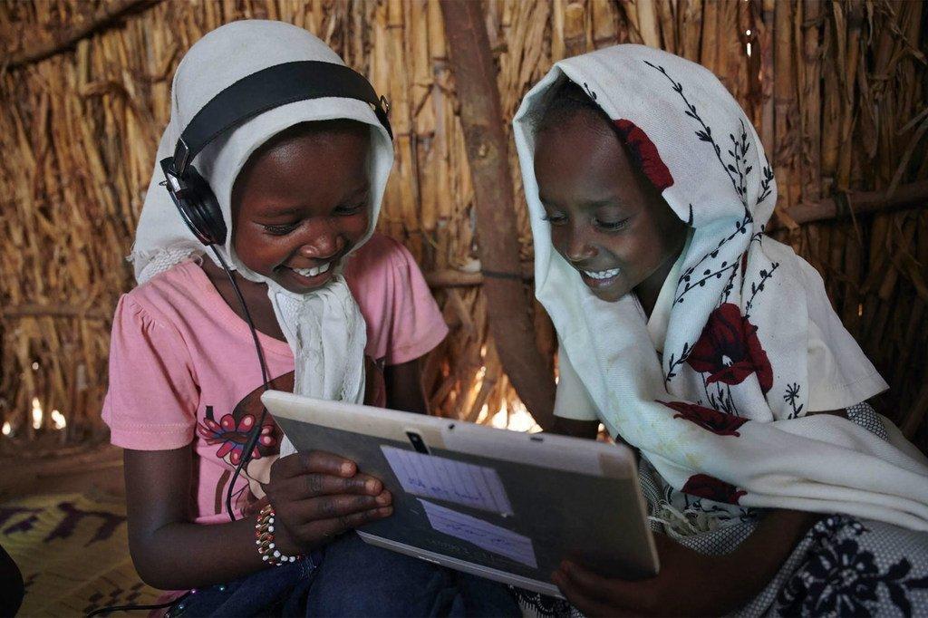 在苏丹东部卡萨拉郊区的一个村庄里,孩子们在联合国儿童基金会支持的学习中心使用平板电脑。