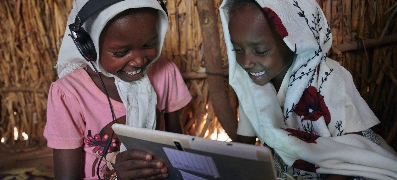 أطفال يستخدمون اللوح الإلكتروني في مركز تعليمي تدعمه اليونيسف في قرية على مشارف كسلا في شرق السودان.