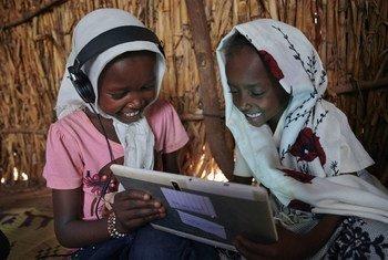 Crianças usam seu tablet em um centro de aprendizagem apoiado pelo Unicef em uma vila nos arredores de Kassala, no Sudão Oriental