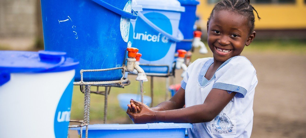 A young girl washes her hands at a primary school in the Democratic Republic of the Congo.