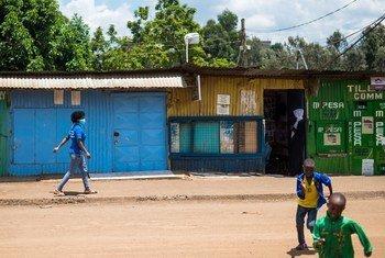 Grace akipita mbele ya duka lililofungwa akiwa anaelekea sokoni Kibera kuelimisha jamii jinsi ya kujikinga na Corona.
