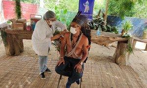Indígena recebe vacinação COVID-19 no Brasil, onde casos de Covid-19 sobem novamente