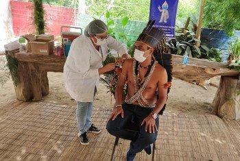 В ВОЗ подчеркивают: чтобы победить пандемию, необходимо обеспечить вакцинацию всего населения планеты. На фото - представитель коренного населения Бразилии получает прививку.