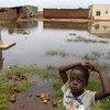 Mtoto akiwa amesimama karibu na pampu ya maji iliyozingirwa na maji ya mafuriko huko Gatumba nchini Burundi.
