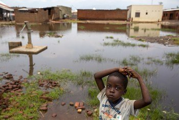 A child stands near a water pump surrounded by floodwaters in Gatumba, located near Bujumbura in Burundi.