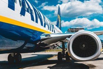 乘客在意大利的机场停机坪上登上一架瑞安航空公司的飞机。