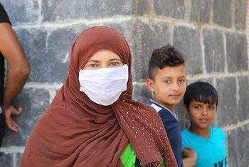 أسر نازحة تنتظر في طوابير للحصول على حصتها الشهرية من الغذاء في دمشق بسوريا.