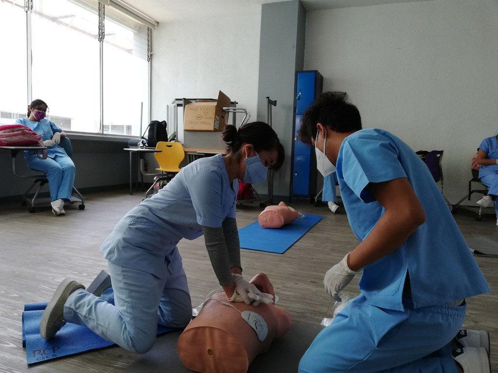 Estuidantes de enfermería practican reanimación cardiopulmonar en un maniquí.