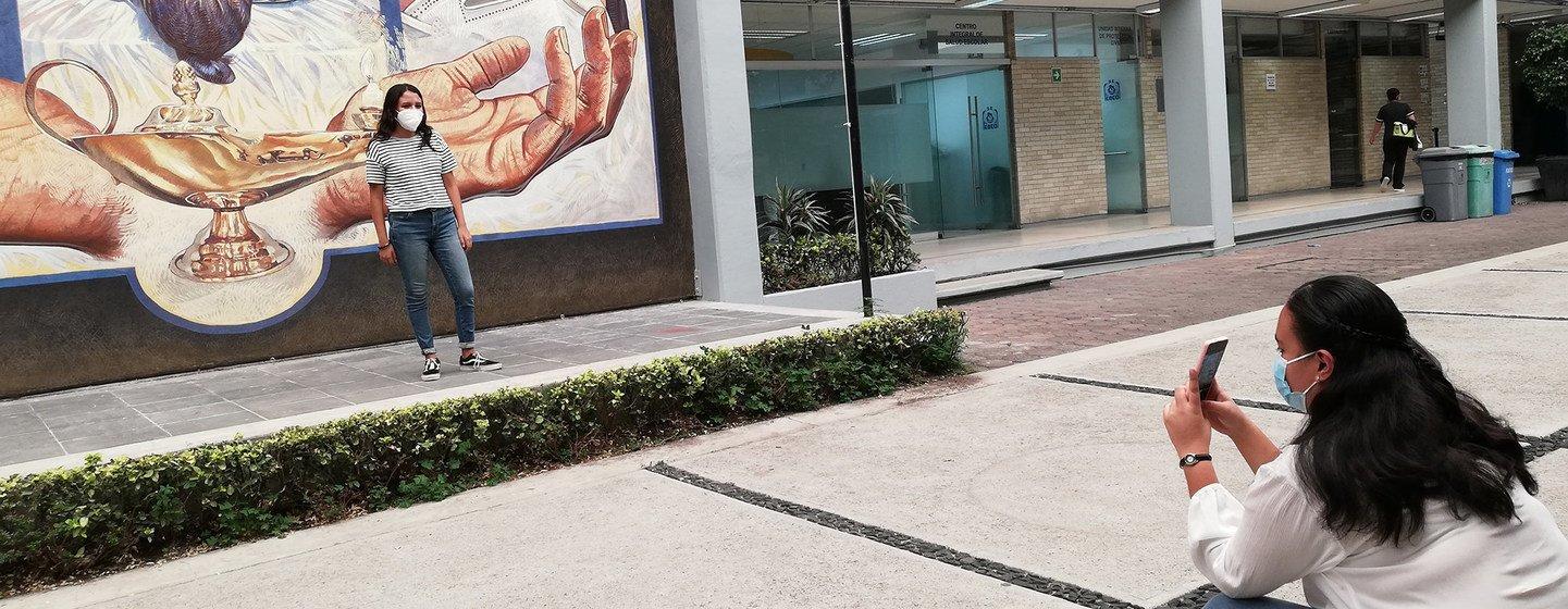 Estudiante de enfermería posa para una foto delante de un mural.