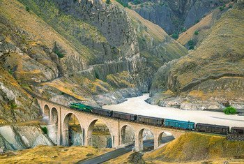A locomotive freight train traverses the Absirom Bridge on the Trans-Iranian Railway in Iran.