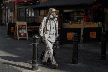 लंदन के वैस्ट एण्ड में मास्क पहने एक व्यक्ति.