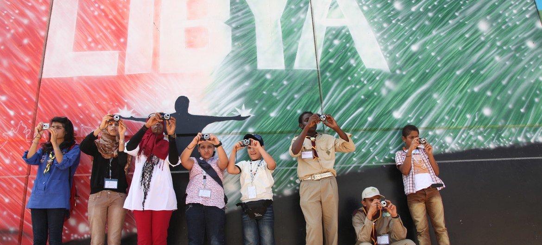 أطفال يشاركون في ورشة تصوير في ليبيا، يلتقطون الصور أمام جدارية في طرابلس. (من الأرشيف)
