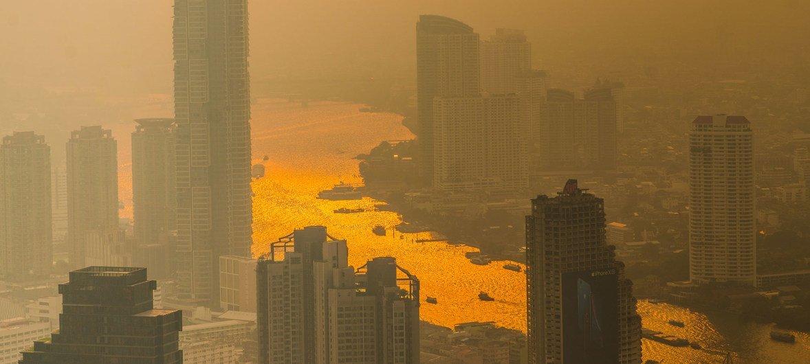 बैंकाक में, चाओ फ्राया नदी पर, छिपते सूरज की रौशनी में, प्रदूषण की परत दिख रही है.