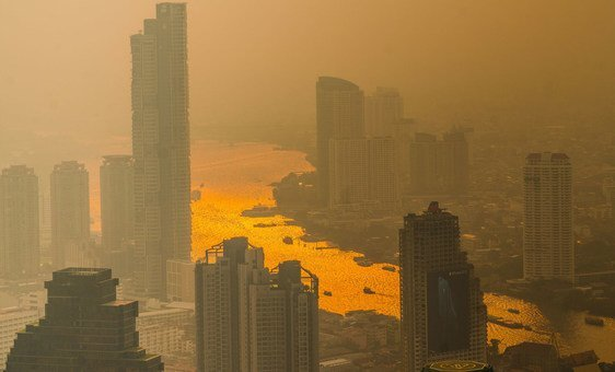 A layer of smog can be seen as the sun sets over Chao Phraya River in Bangkok.