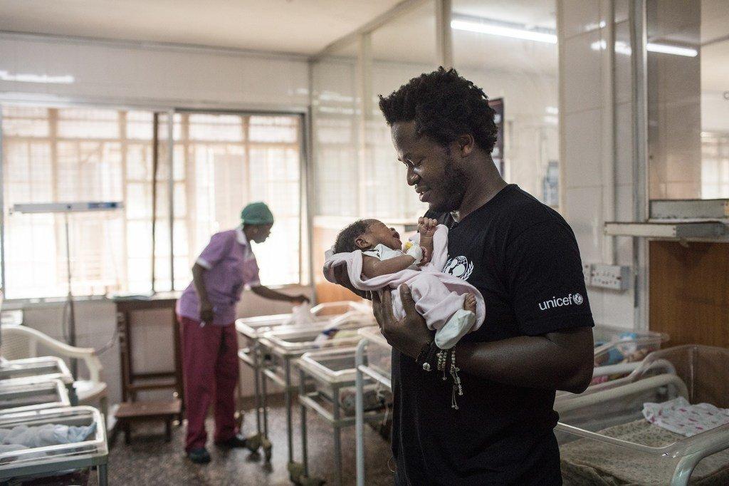 Ishmael Beah, mwandishi wa vitabu, askari mtoto wa zamani na Balozi mwema wa  UNICEF kuhusu watoto walioathirika kwa vita akiwa amebeba mtoto njiti katika hospitali ya Ola During, mjini Freetown nchini Sierra leone.