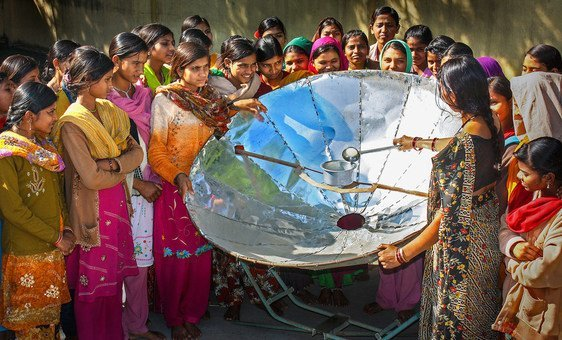 In India, a woman demonstrates how to use a solar dish for cooking.