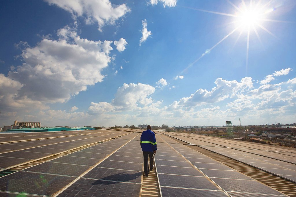 Un técnico examina paneles solares en el techo de un almacén en Lusaka, en Zambia.PNUD/Karin Schermbrucker