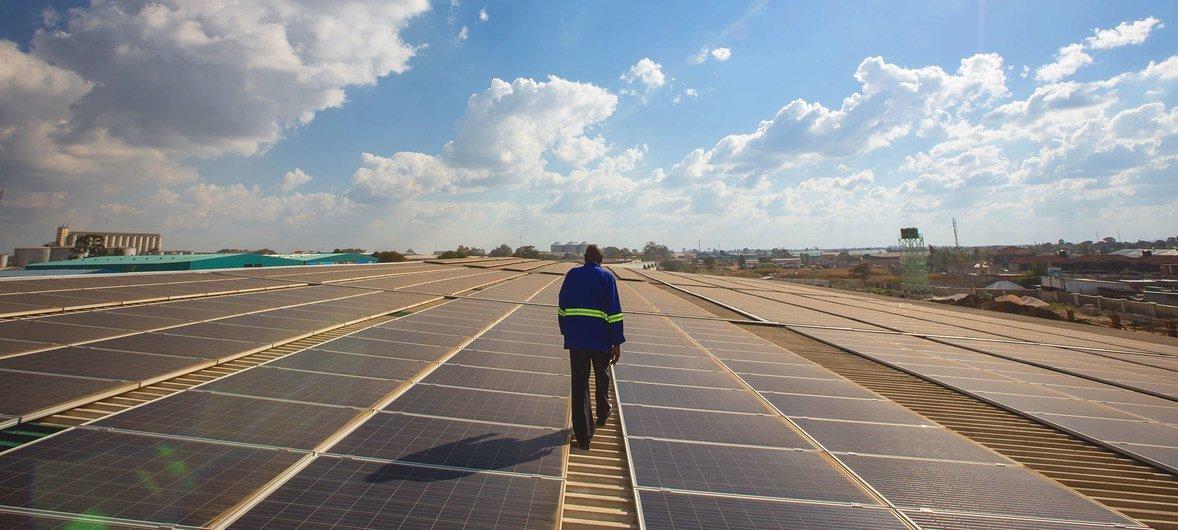 Técnico trabalha em painéis solares no telhado de um armazém no centro de Lusaka, Zâmbia