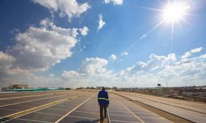 Un technicien s'occupe de panneaux solaires sur le toit d'un entrepôt à Lusaka, en Zambie.