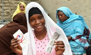 In the center of Chad, 19-year-old Achta holds up condoms during an HIV awareness-raising session in her Moussoro community. (March 2019)