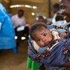 Mama akiwa amembeba bintiye mchanga akimwandaa kwa ajili ya kupata chanjo kadhaa katika kituo cha chanjo kilichofadhiliwa na UNICEF katika jimbo la Kivu Kaskazini nchini DRC.