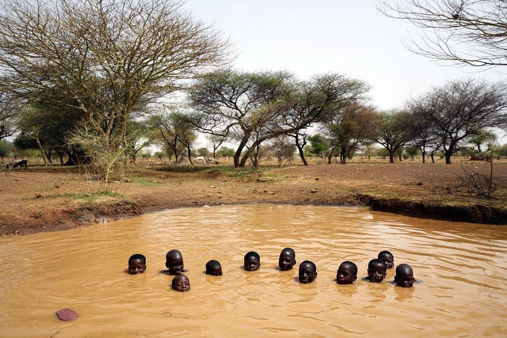 فتيان يلعبون في حفرة مائية بالقرب من بلدة كايا في شمال بوركينا فاسو.