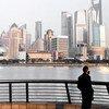 一位戴着口罩的市民伫立在上海外滩。为应对新型冠状病毒疫情,中国民众大都待在家中避免外出,一贯熙熙攘攘的外滩也难得地安静了下来。