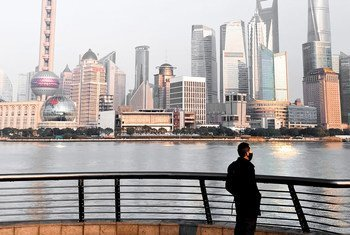A resident of Shanghai, looks out over the city waterfront, known as the Bund, which is usually a crowded tourist hotspot.