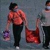 Dos mujeres en Shenzhen, China, de camino al trabajo en medio de la epidemia del coronavirus.