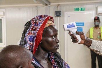 Integrante de un equipo médico mide la temperatura de una mujer desplazada en Sudán del Sur.