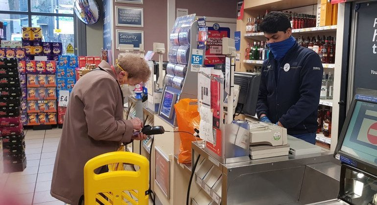 An elderly customer buys provisions at a shop in a South London suburb in the UK.