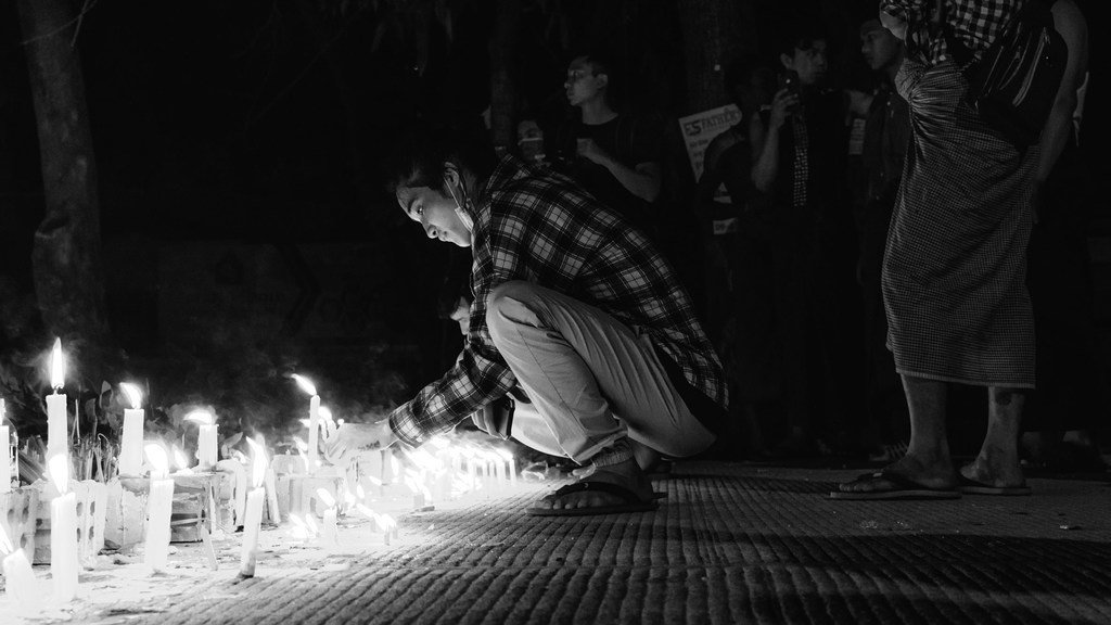 缅甸仰光,一名年轻男子在守夜期间点燃蜡烛。