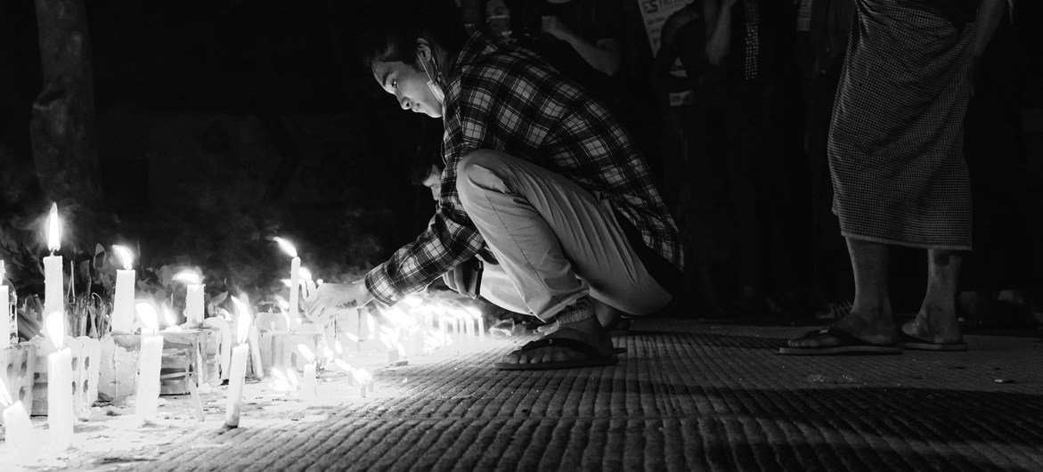 Un joven ilumina una vela en Yangon, en Myanmar.