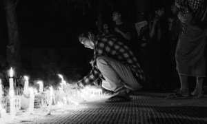 Young man lights a candle during a night vigil in Yangon, Myanmar.