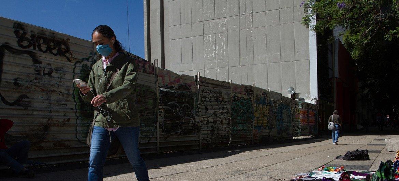 Un peatón camina mirando su teléfono móvil por las calles de la Ciudad de México durante la pandemia de COVID-19.