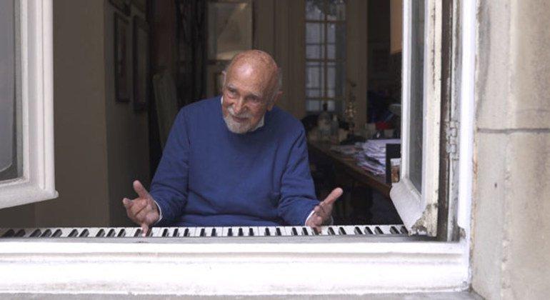 Simon Gronowski toca el piano para los transeúntes desde su casa en la ciudad belga de Bruselas.