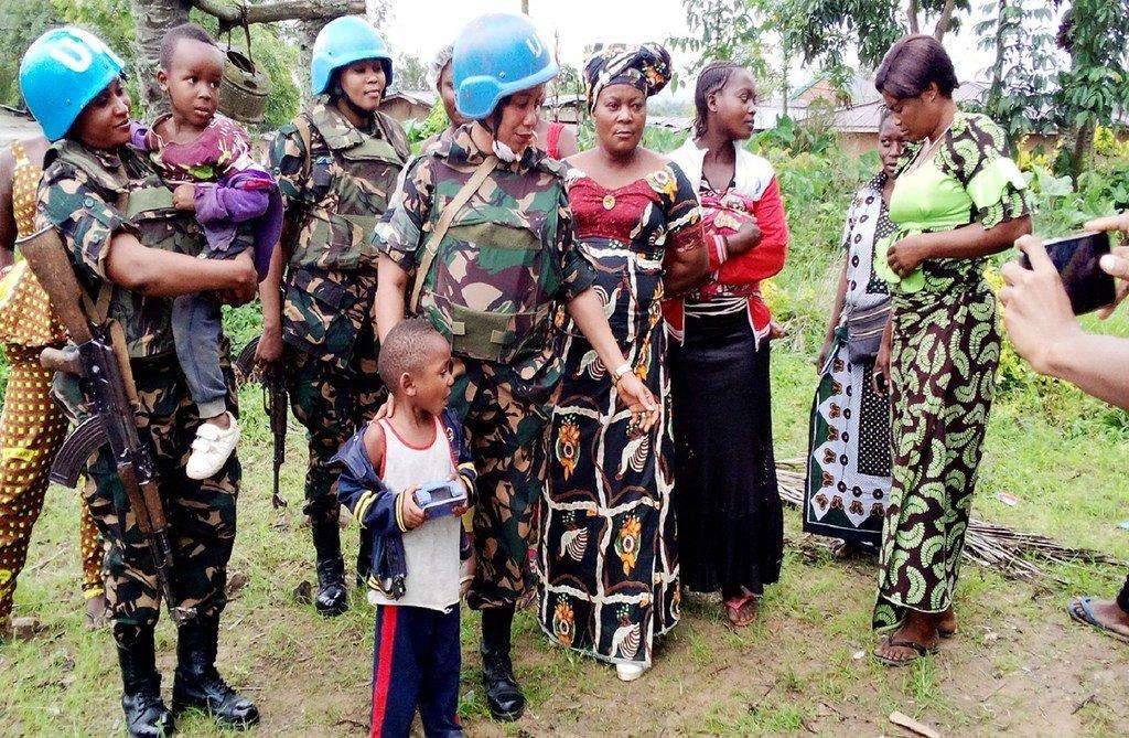 来自坦桑尼亚的女性维和人员与刚果民主共和国贝尼地区的妇女和儿童在一起。