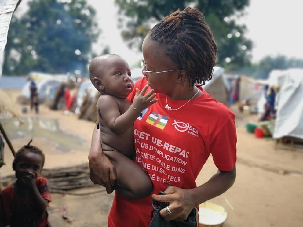 Reporter et animatrice centrafricaine de Guira FM, Merveille Noella Mada-Yayoro tient un enfant dans le camp de déplacés de Birao.
