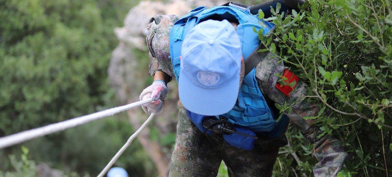 刘熙平在蓝线维护途中攀越崖壁