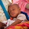 Un bébé dort dans les bras de sa mère dans un centre de santé maternelle et infantile en Mauritanie pendant la Semaine africaine de la vaccination.
