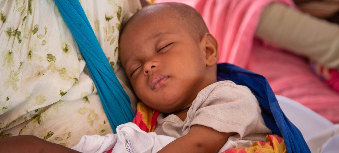A baby sleeps in his mother's arms at a mother and child health centre in Mauritania during African Immunization Week.