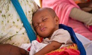 Un bebé duerme en los brazos de su madre en espera de recibir una vacuna.