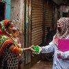 A Dhaka, la capitale du Bangladesh, une agente de santé distribue des fournitures d'hygiène à une famille