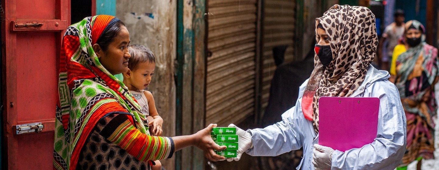 一名卫生工作者向孟加拉国达卡的一个家庭分发卫生用品。