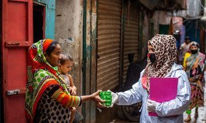 A health worker distributes hygiene supplies to a family in Dhaka, Bangladesh.