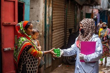 إحدى العاملات الصحيات توزع مستلزمات نظافة على الأسر في بنغلاديش.