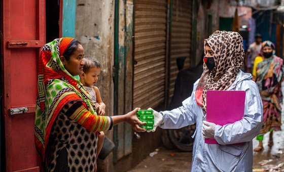 Funcionária de saúde distribui itens de higiene no Bangladesh, para prevenir Covid-19